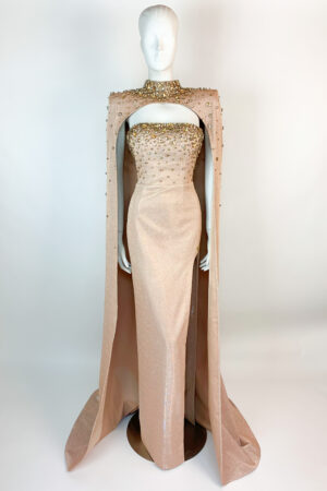 Gold shimmer column gown with high neck cape and elaborate gold jewels